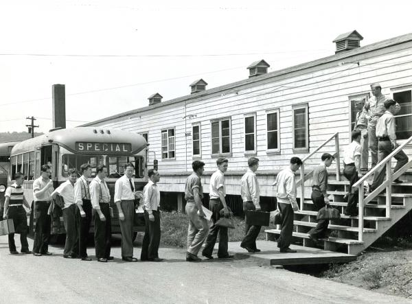 Photograph of New Cumberland Inductees departing a bus and entering into a barracks.
