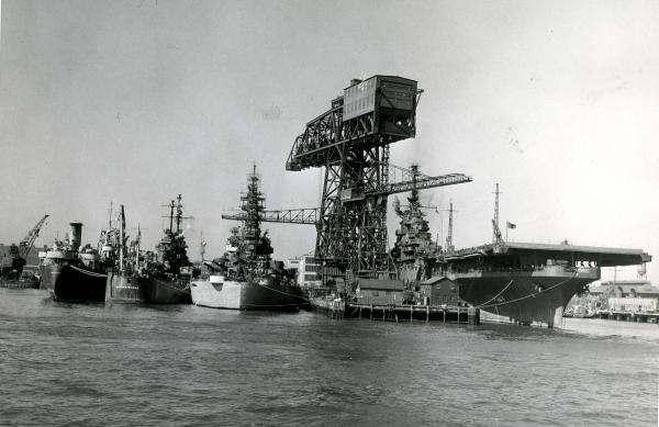 Fighting ships of the U. S. Navy moored alongside its famous hammer-head crane, Philadelphia Naval Shipyard.