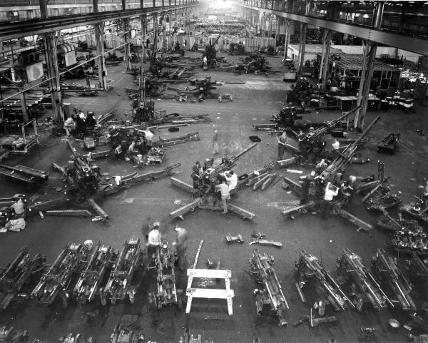 Image of an interior factory with guns and employees