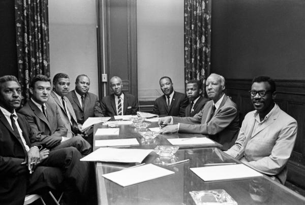 Black and white photograph of civil rights leaders in suits seated around a conference table with papers in front of them.