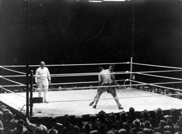 A crowd surrounds a boxing arena as two men fight and a referee looks on.