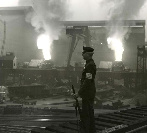 A dark image of a Military Policeman standng guard at the steel plant.