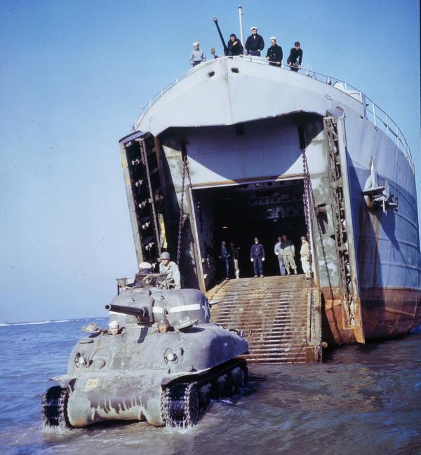 Color photograph of a LST landing with soldiers and a tank disembarking.
