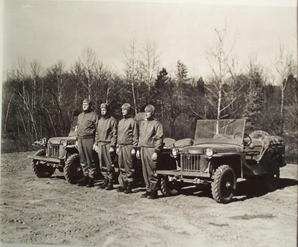 Photograph of three jeeps and four men standing in front of them, posing for this photo.