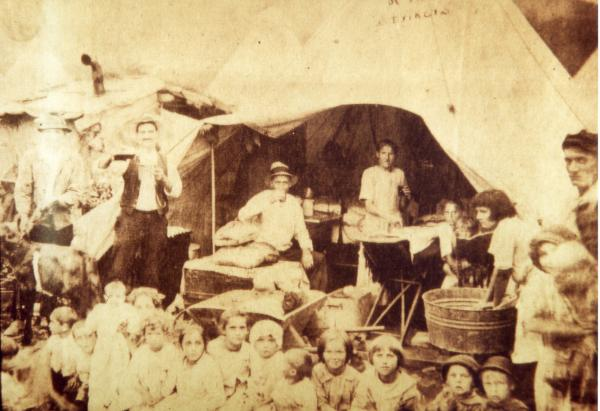 A tent colony scene, with children sitting outside posing for photograph. Miners and their wives sit and stand behind them, both inside and outside of the tent structure. One young girl to the right of the photograph is washing clothes in a metal tub.