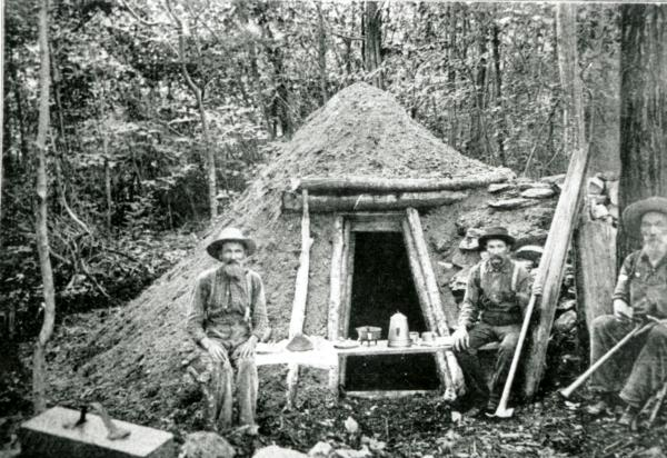 Three workers sit outside the entrance to a crude hut.
