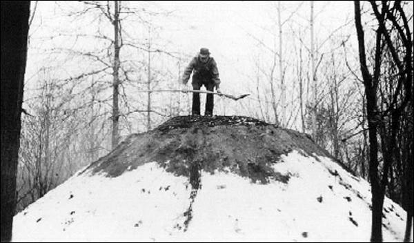 This photo shows Lafayette Houck, the last of the Hopewell colliers, in a 1936 demonstration of charcoal-making at Hopewell Furnace. Mr. Houck is walking on the burning pile to find soft spots, which had to be dug out and filled in to maintain even burning.