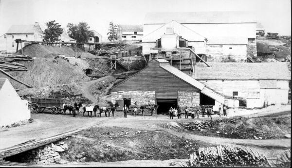 Springfield Furnace showing workers lined up, with children, tools, mules, and wagons. The complete iron works can be seen in the background.