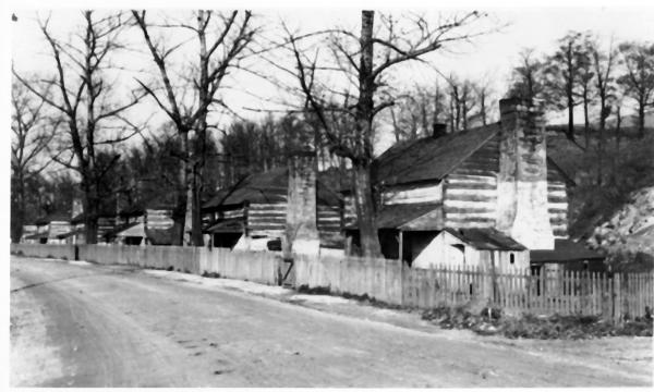 Row of cabins inside a pickett fence.