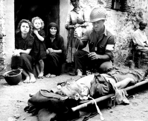 Army private Roy W. Humphrey's receiving blood plasma after he was wounded by shrapnel in Sicily, August 9, 1943.