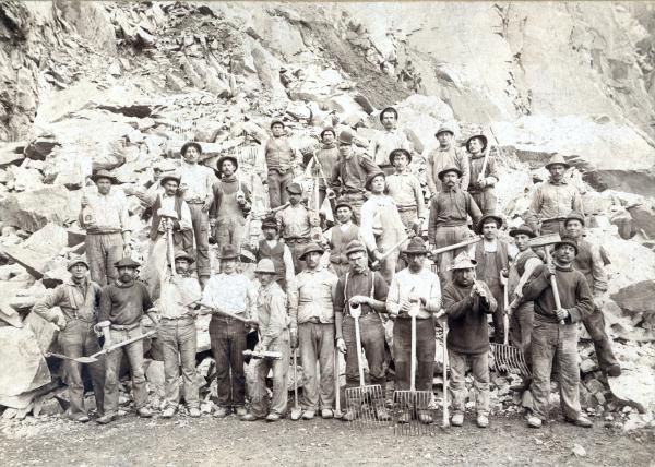 Black and white photograph of a large group of iron workers, each holding a tool.