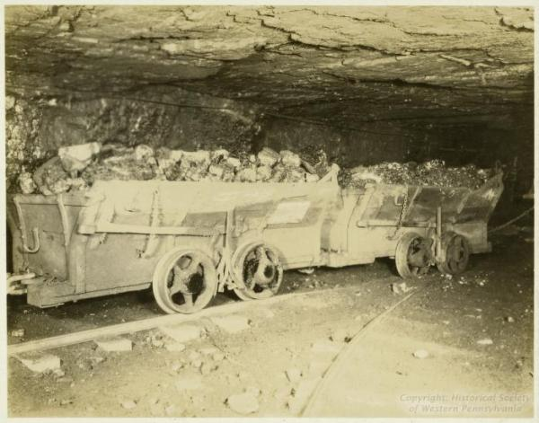 Photograph shows loaded coal cars in the mine.
