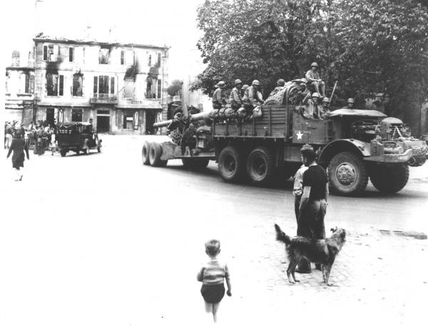Image of truck with soldiers riding in the back making its way through a town as citizens of Brest, France watch.