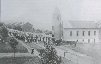 Image of the church, people standing outside, and company housing can be seen in the background.