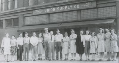 A row of men and women pose for a photograph in front of the Company store.