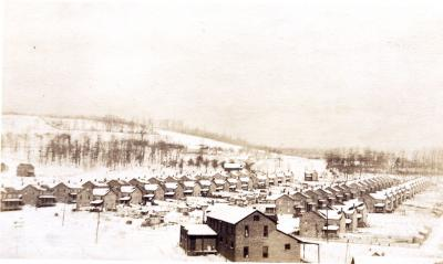 Snow covered roofs of houses and the ground paint a bleak picture of this coal patch town.
