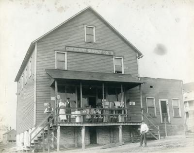 A black and white photograph of a wooden company store with a large porch. Two employees and several small children stand on the porch. One employee stands on the steps extending from the left of the porch. One man stands in front of the store, to the right of the photograph. There is a sign above two windows that reads: Crescent Supply Co.