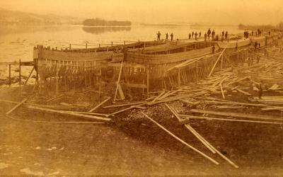 Workers stand along the tops of two long rows of canal boats and along the side of wooden scaffolding that holds the boats that are in process of being constructed.
