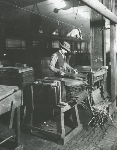 American Sheet and Tin Plate Company worker trims tin plate.