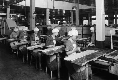 A black and white photograph of women sitting at tables, and manually affixing labels to the jars.
