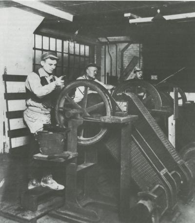 Three men holding large panes of glass against a belt, stand in back of wheels that carry the sharpening belts.