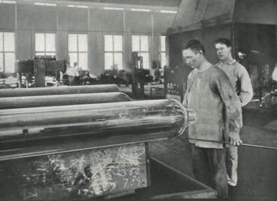 A worker is capping off window glass cylinders preparatory to flattening, while another worker look on.