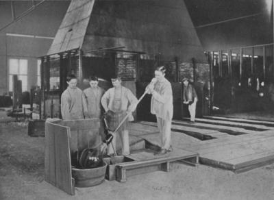 A glass blower works with a blowing iron and molten glass to blow a window-glass cylinder. Other workers are observing the task.