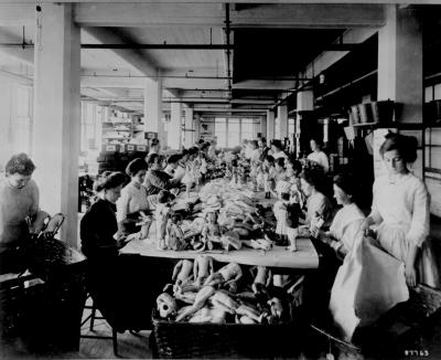 Women assembling dolls on a long worktable at the Shrenhat Toy Company