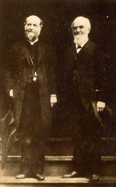 Two men in suits, standing side by side at an entranceway, pose for this full length portrait.