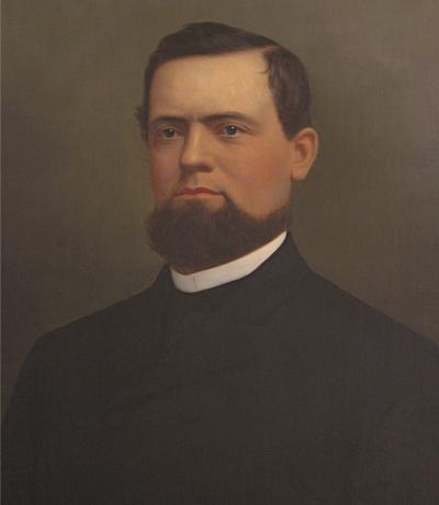 Oil on canvas, head and shoulders of a bearded man wearing a black suit and a white shirt.