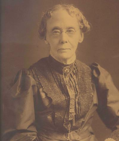 Sepia photgraph of an elderly lady. She is wearing a dress with a ruffled front and spectacles.