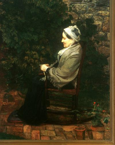A profile of an elderly lady wearing a long dress, tan shawl, and a bonnet, sits knitting, in a chair on the brick patio of the garden.