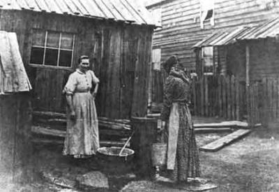 Mine owners constructed and rented shanty-type houses to their workers, mostly immigrant laborers.  Here, women are drawing water from one well, which had to supply twenty-five families.