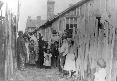 A group of adults and children assemble for this photograph between two plank fences in their