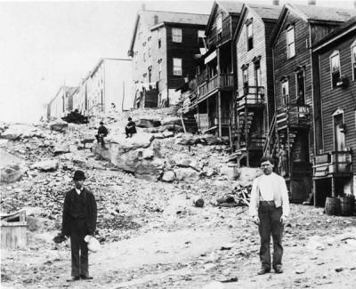 Houses and boarding house face what appears to be a culm pile.  Several residents of the town pose for the camera.