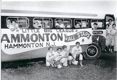 A black and white baseball card of the Hammonton New Jersey All star team bus. Four team members kneel beside the bus and other team members peer from each window and stand in the doorway.