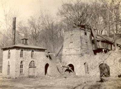 Image of an old blast furnace. There is a small brick building with arched windows next to the furnace.