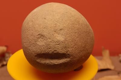 Simple carvingof a face on stone cobble.