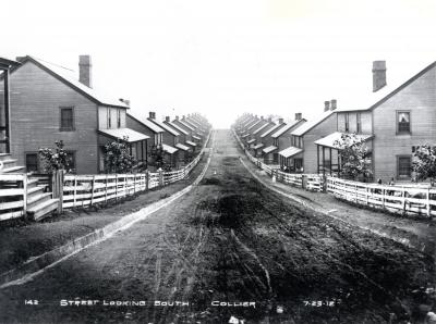 Homes bordered by white picket fences line the dirt street. People are sitting on porches and children can be seen in the road and outside several of the fences. In the first home on the right on the second floor one can see white curtains hanging in the window.
