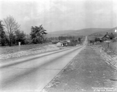 Paved road with with Esso station on left hand sign.