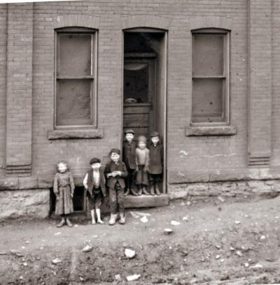 A group of immigrant children stand in a doorway in Johnstown.