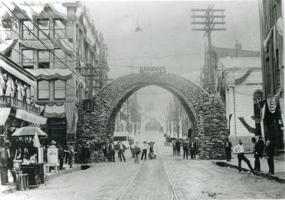 A huge coke arch stretches across the width of a street. On the top of the arch is a sign that reads: HCFC Co. People are standing under and to either side of the arch, as well as along the city street. Directly underneath the center of the arch, a young boy kneels with his arms around his dog's neck. Banners and flags hang from the buildings. To the right of the photograph are vendors and a large barrel that reads