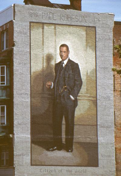 Mural painting of Robeson, standing, wearing a three pice suit.