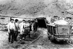 Workers and superintendent line up for photograph at the entrance of a mine. A coal car sits at the right of the picture.