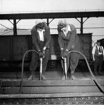 Two women dismantling the side of an old hopper car.'