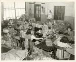 A room of female seamstresses sew parachutes for the war effort.'