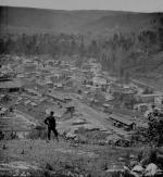 This photograph was taken overlooking the Bloss rail yard and also shows the down town section. One lone man stands at the top of the overlook.