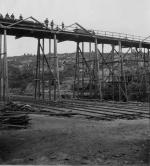 Men standing along the top of the trestle pose for a photograph.
