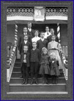 William and Agnes Wilson with their children posed along the steps of their home. First row (L-R) James, Joseph, Elizabeth and Jessie. Second row (L-R) Tom, William and Mary. Third row (L-R) Hugh, Agnes and Adam