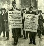 Two picketers wearing their mining hats and head lamps carry signs and stop to pose for photograph: Picketer on the left sign reads: Put our wives back into houses, take your armed guards away from the mines, 20,000 Pa. Miners on strike, protest against inhumane tactics of Berwind White Coal and II Broadway.  Picketer on the right sign reads: Berwind evicts women and children. Why Not Settle. Other people are standing behind the two picketers.